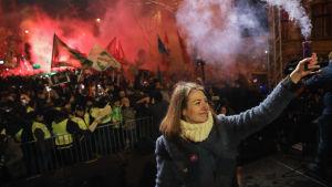 Kvinna håller i en rökgranat och i bakgrunden syns demonstranter.