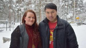 En bild på en kvinna och en man som står med snö i bakgrunden