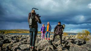 Kaksi henkilöä poseeraavat tv-kameralle kivien päällä järvi taustallaan. Etualalla kameramies ja avustaja.