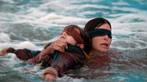 En bild från filmen Bird Box – två personer i vattnet med ögonbindlar.