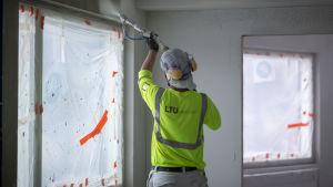 Rakennusmies työssään Skanskan kerrostalokohteessa tasoittamassa seiniä ja kattoa ruiskutasoitteella, Munkkiniemi, 25.1.2019.
