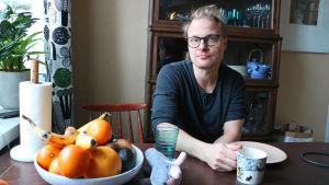 Skådespelaren Paavo Kerosuo sitter vid sitt köksbord.