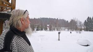 En äldre man ser ut över ett snötäckt landskap.