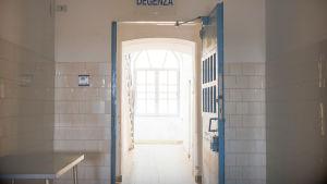 vy i mentalsjukhus från mörkt rum med blå dörr med lås mot ljust fönster