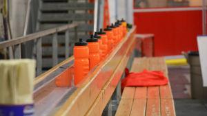 orange dricksflaskor på bänk