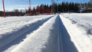 Koneella ajettu latu-ura Helsingin Paloheinässä. Talvi, pakkaspäivä ja aurinko paistaa.
