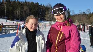 Ellen Strömborg (till vänster) och Daniela Sandås står vid en skidbacke.