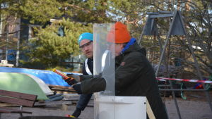 Två män, den ena med turkos mössa och den andra med orange mössa, förbereder sig i en övning att skjuta iväg en nödraket. De skyddar sig bakom en plexiglasskiva.