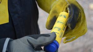 En person läser på ett nödbloss, en gul tub med bruksanvisningar för hur nödblosset ska användas.