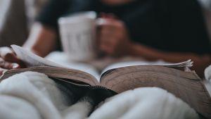 En människa sitter i en fåtölj och läser en bok.