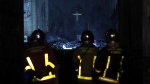 Brandmän vid Notre-Dame, som brinner.