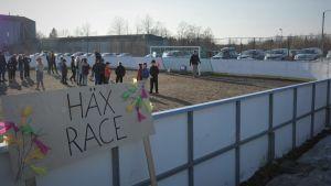 """En skylt med texten """"Häxrace"""" vid en fotbollsplan. Flera barn deltar i en tävling i bakgrunden."""