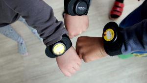 tre dagisbarn sträcker fram sina händer där de har varsitt aktivitetsarmband på.
