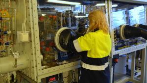 Tarja Korvenoja har händerna inne i stora svarta plasthandskar i laboratoriet i en glasmonter.