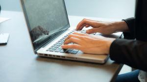 Händer skriver på tangentbord