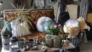 Inredningsprylar på ett bord med en soffa med kuddar i bakgrunden i Amalias hem