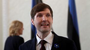 En man står i kostym - i bakgrunden syns Estlands flagga