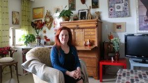Lena Bengtson sitter i en fåtölj i sitt vardagsrum och ser bestämd ut.