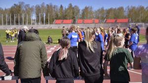 en grupp flickor med ryggen till kameran följer med en stafettlöpning på en idrottsplan