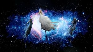 kate som sjunger för australien står tillsammans med två dansare iklädd i svart och själv i vit klänning på tre cirkuspålar med en bild av universum i bakgrunden