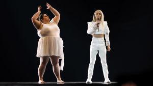 bilal hassani i vit dräkt sjunger bredvid en dansare som för ovanlighetens skull inte är smal
