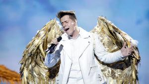 roko sjunger för kroatien i esc 2019 och har en vit dräkt med stora fjädervingar i guld på ryggen