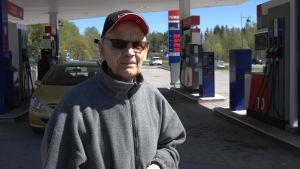 Man som står vid bensinstation.