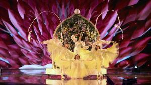 katerine duska uppträder med gulklädda balettdansare och en stor blomvägg bakom