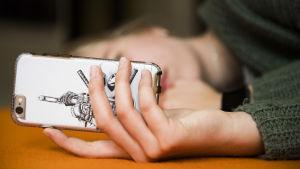 Flicka ligger på en soffa och ser på mobiltelefonens skärm.