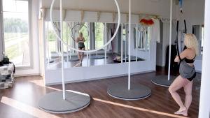 En kvinna i en gymnastikstudio med speglar.