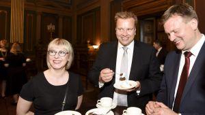 Leende ministrar äter tårta.