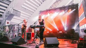 Vaaleahiuksinen nainen aurinkolasit päässään soittaa kitaraa lavalla, toinen vaaleahiuksinen nainen soittaa syntetisaattoria. Taustalla on savua ja valkeaa ja punaista valoa.