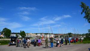 Grupp med människor står och väntar på att en fisketävling ska börja.