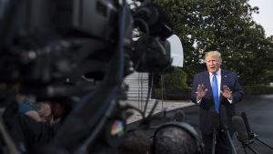 Donald Trump svarar på journalisternas frågor utanför Vita huset.