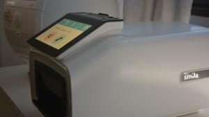 En sorts läkemedelsrobot, som i princip ser ut som en vit låda med en pekplatta på sig. På bilden meddelar maskinen att nästa medecin ska tas klockan 10:00.