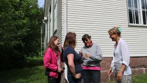 Tre kvinnor och en ung flicka står och talar framför en vit skolbyggnad. De ser glada ut och gestikulerar.