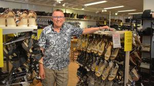 En bild på en man, Tapio Viljanen, som står omgiven av ställningar med skor, främst sandaler.