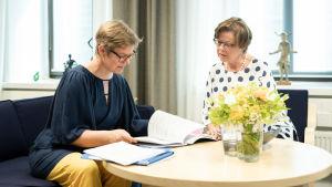 Krista Mikkonen ja sihteerin Kristina Tamminen neuvottelevat.