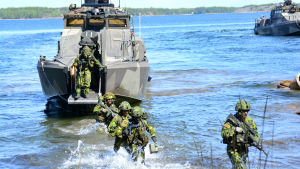 svensk militär personal vadar i vatten från båt