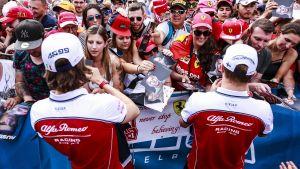 Antonio Giovinazzi och Kimi Räikkönen skriver autografer.