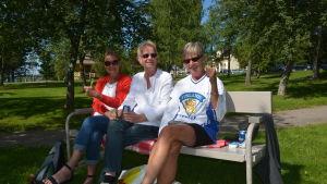 Tre leende personer i solglasögon sitter på en parkbänk med träd i bakgrunden.