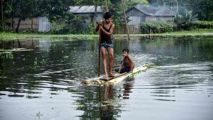 Två indier tar sig genom en flod.