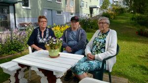 Två kvinnor och en man sitter vid ett vitt bord framför ett höghus.