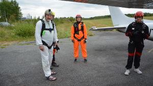 Fyra personer iklädda fallskärmshoppningsutrustning står bredvid ett flygplan.