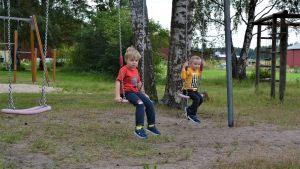 Två pojkar sitter och gungar på en skolgård. I bakgrunden syns träd och en klätterställning.
