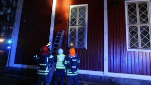Brandmännen pekar på fönstret som nästan fattade eld.
