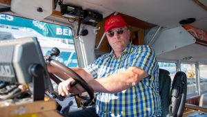 Svante Wilson i ratten på båten Minandra.