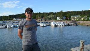 En man står på en brygga med flera bryggor med båtar i bakgrunden.