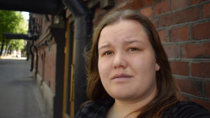 En kvinna står framför en tegelvägg och tittar in i kameran.