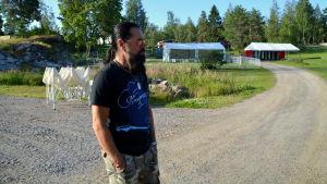 En man står framför vita festivaltält.